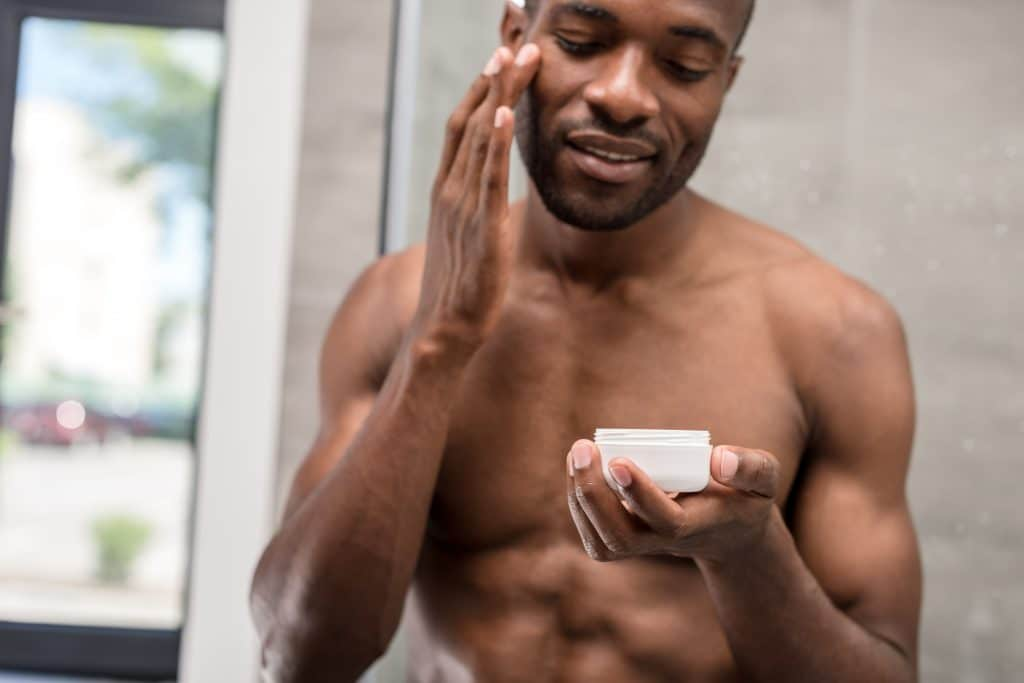 Smiling,Shirtless,Young,African,American,Man,Applying,Facial,Cream,In